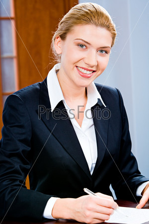 Portrait of beautiful business woman holding a pen  looking at camera
