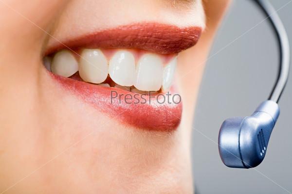 Рот и зубы улыбающейся женщины с микрофоном, крупным планом
