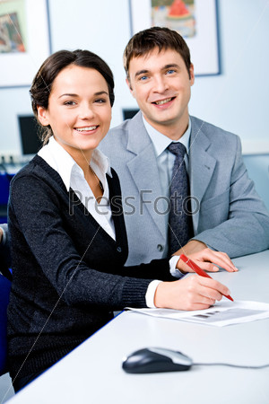 Портрет двух успешных студентов, сидящих за столом в компьютерном классе и улыбающихся