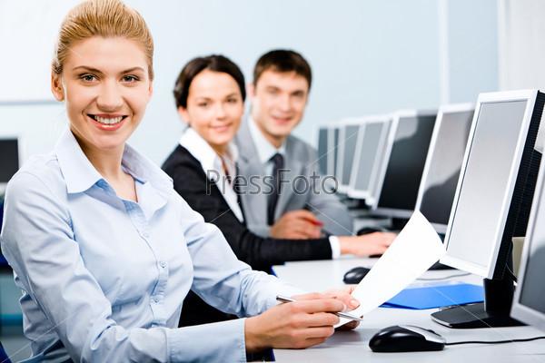 Трое студентов, сидящих в ряд в компьютерном классе с улыбками