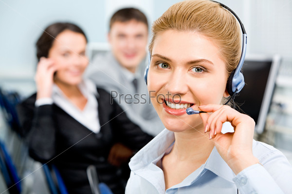 Closeup of smiling beautiful business woman with headset on the background of her business partners
