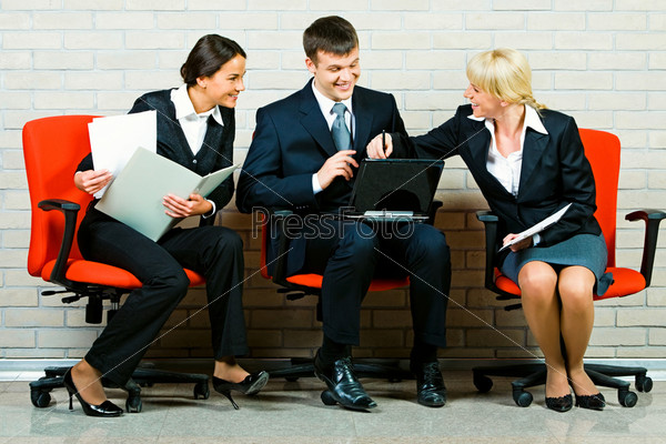 Portrait of business people sitting on the red armchairs and discussing a new idea