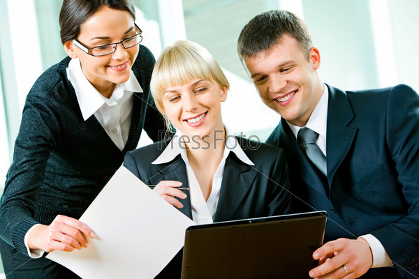 Group of three business people looking at monitor of laptop