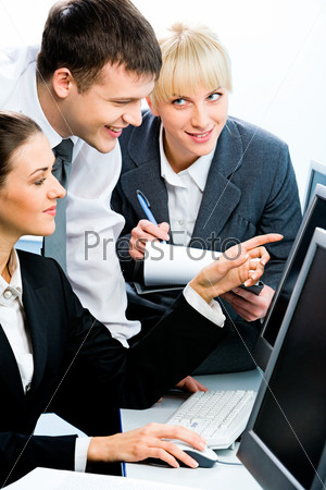up of three smiling businesspeople sitting at the desk before the computer looking at its monitor