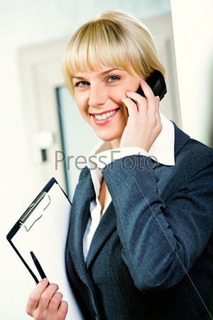 Image of a young attractive businesswoman calling by phone holding the folder