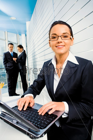 Successful woman doing some computer work on the background of business people in the office