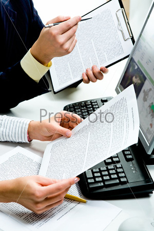 up of businesspeople's hands holding documents with computer near by