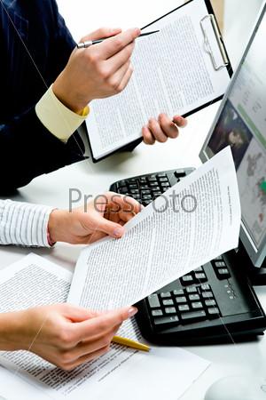 Руки деловых людей с документами, рядом с компьютером