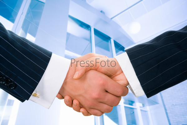 Image of businesspeople handshake on the background of office building