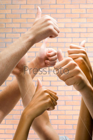 Image of human hands showing sign of okay on the background of brick wall