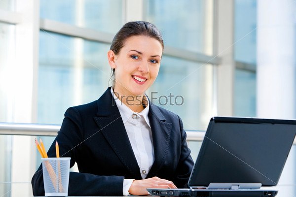 Portrait of confident employee sitting at the table and typing a document on the laptop on the background of business people