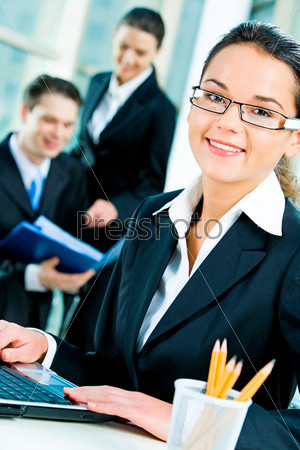 Successful young woman with glasses looking at camera in a business environment