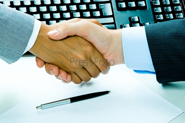 Image of two business people's handshake after making an agreement on the background of keyboard, pen, paper