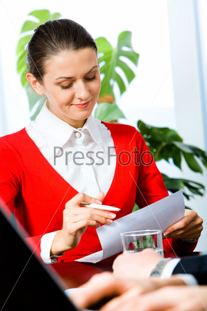 Portrait of pretty woman reading a document in the office