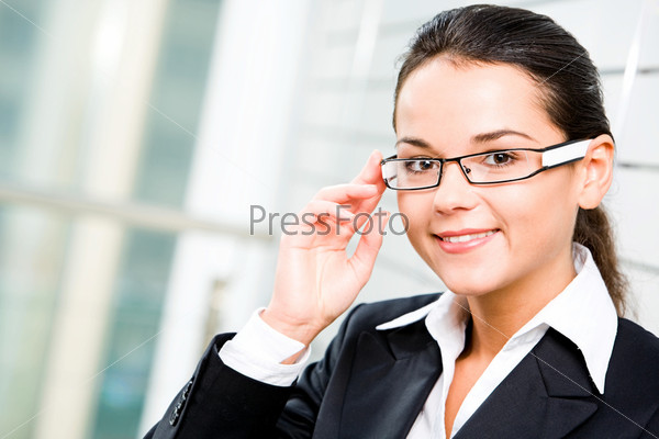 confident woman in suit touching her glasses