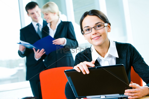 Image of professional with glasses touching her laptop in a working environment