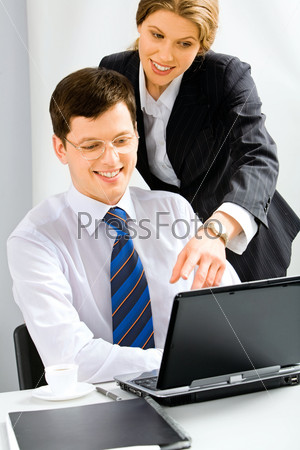 Executive secretary is explaining the correct way of report to her boss pointing at the monitor of laptop
