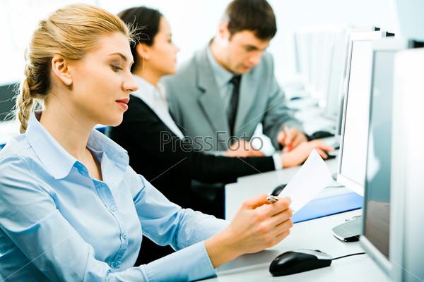 Студентка сидит за столом с бумагой и ручкой