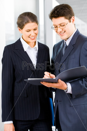 Portrait of two business people standing in the office