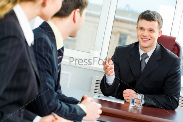 Confident boss proposes new terms of transaction to business partners at meeting
