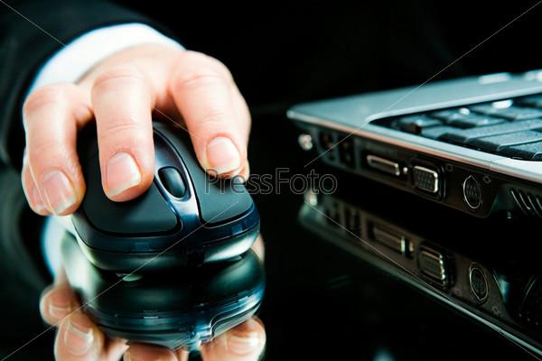 Рука на компьютерной мышке рядом с ноутбуком