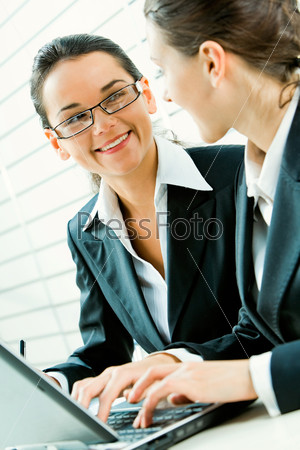 Portrait of business woman with glasses gazing at her colleague and smiling