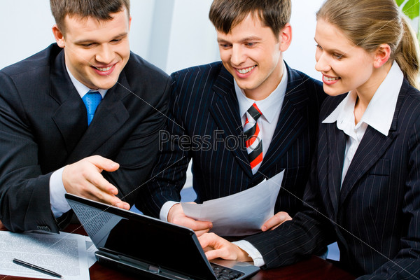 Portrait of three young specialists looking at monitor of laptop