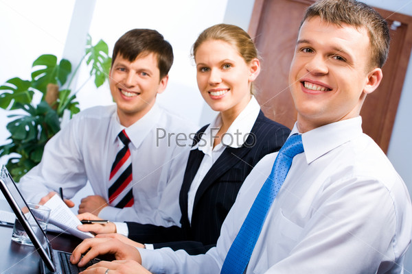 Row of three business people sitting at the table and looking at a camera