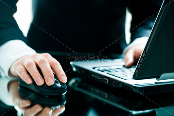 Image of businesswoman's hand on the mouse with a laptop near by