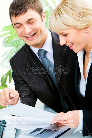 Vertical image of two business colleagues discussing business documents