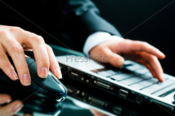 Image of human hands working on the laptop and computer mouse