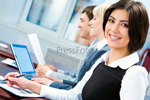 Portrait of smiling business woman looking at camera during working briefing