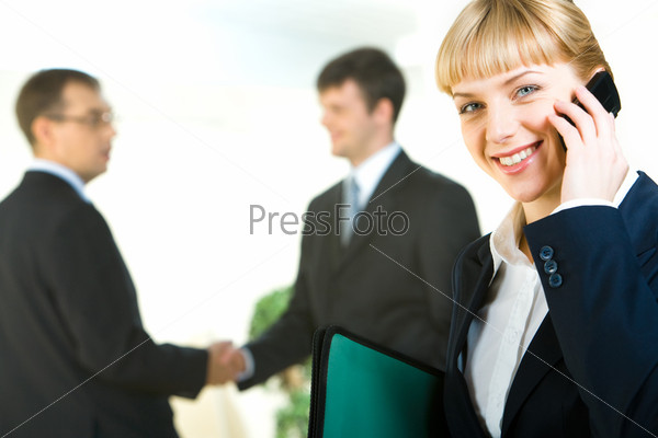 Вusiness woman calling on the phone on the background of people shaking hands