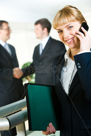 Photo of attractive employee speaking on the mobile in a working environment