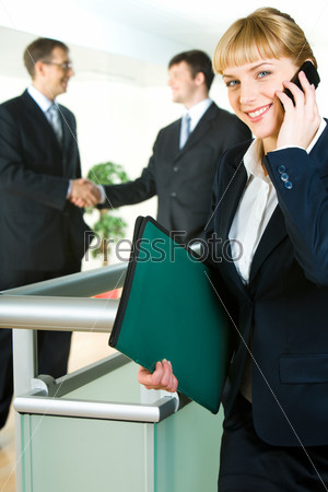 Image of confident woman holding the folder and phone