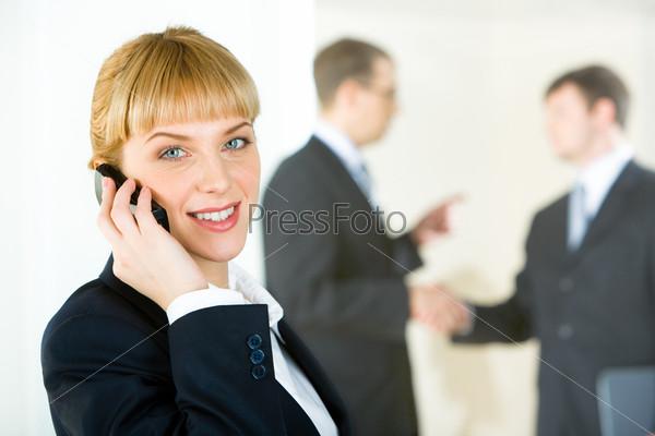 Консультант говорит по телефону на фоне деловых людей