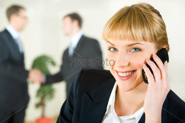 View of attractive smiling businesswoman speaking on the mobile looking at camera