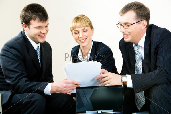 Image of three business people looking at the document at meeting