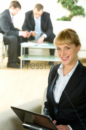 Portrait of business woman sitting on the sofa and holding laptop in the office building