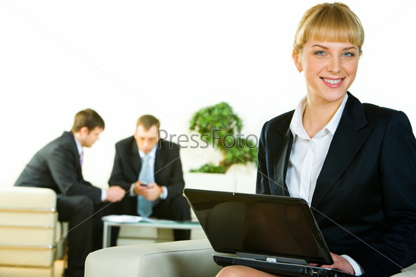Photo of employee looking at camera and holding the laptop