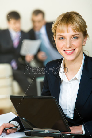 Portrait of beautiful employee on the background of her coworkers