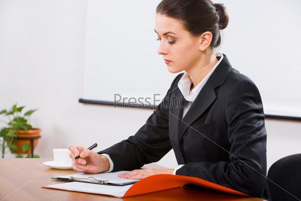 Фотография на тему Деловая женщина сидит за столом и работает с документами