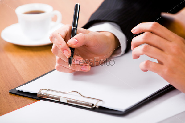 Вusinesswoman's hand holding pen over white paper with a cup of coffee near by