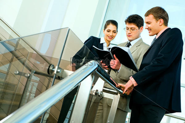 Photo of business partners standing in the office block and looking into business plan