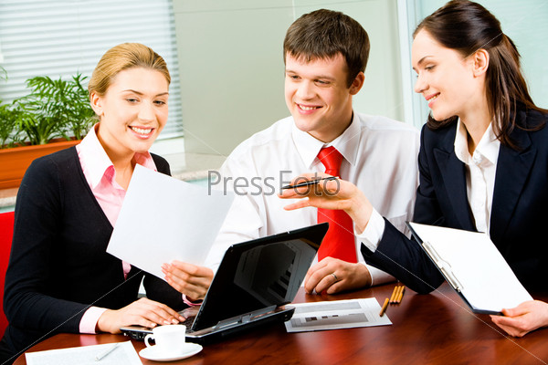 Portrait of three businesspeople working at the table in the office