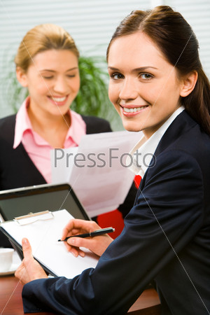 Portrait of a young smiling businesswoman sitting in the office with documents