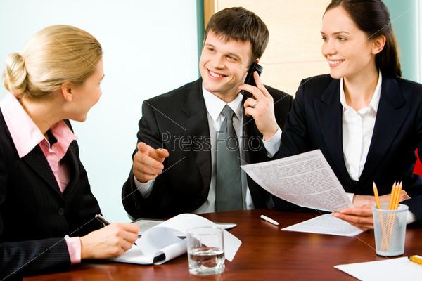 Бизнесмен говорит что-то коллеге при разговоре по телефону