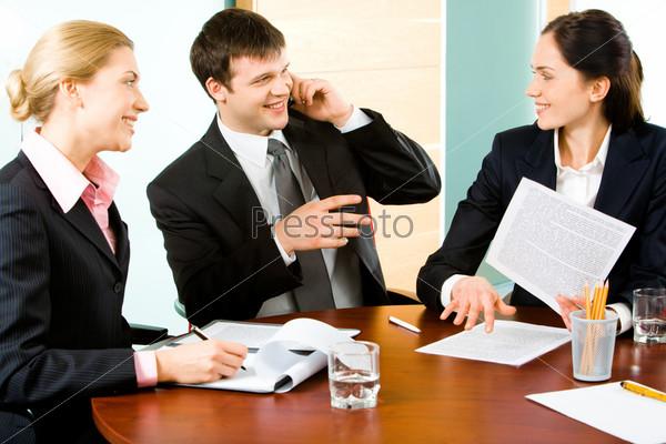 Трое деловых людей общаются в рабочей обстановке