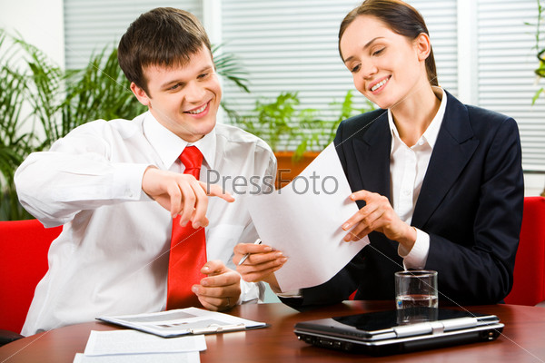 Portrait of business man explaining a new project  to woman pointing at the document