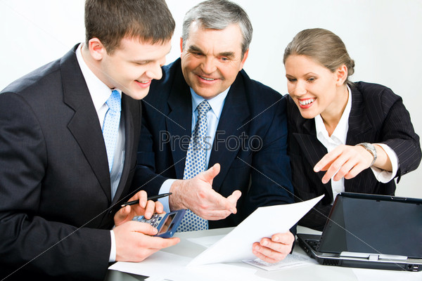 Photo of three colleagues working with papers and looking into one document